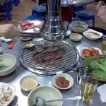 BBQing tasty thin beef strips (bulgogi) on tabletop charcoal grill (with duct above it) and banchan