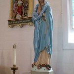 Statue of Mary in the church (what is she standing on, besides a pedestal?)